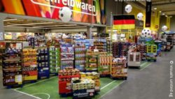 Image: Sweet section in a store. A part of the floor has a look of a football field; Copyright: visuals united ag