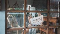 "Photo: Woman hangs ""open"" sign in the shop window; copyright: panthermedia. net / odua"