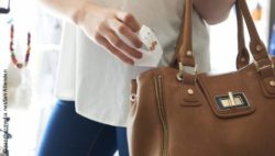 Image: woman puts a product into a handbag; copyright: panthermedia.net/Ian Allenden