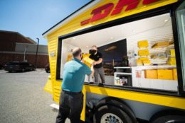A mobile truck in DHL colors with a employee handing a customer a package; Copyright: PRNewsfoto/DHL
