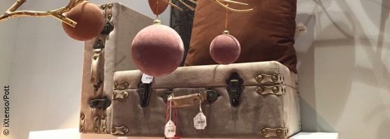 velvet Christmas baubles in front of a velvet suitcase in brown shades; copyright: iXtenso/Pott