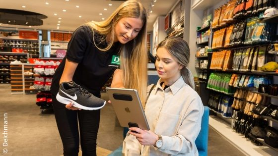 A saleswoman advises a customer with a tablet PC in a shoe store; copyright: Deichmann
