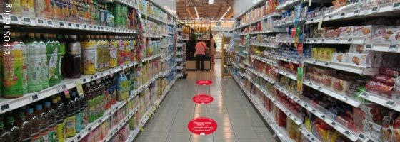 An aisle between two supermarket shelves with red stickers on the floor; copyright: POS Tuning