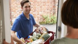 Photo: Delivery man hands over a food crate to a woman at the front door; copyright: panthermedia.net / Ian Allenden