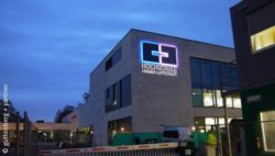 "Image: Builing at night. On the building is written in illuminated letters: ""Collage Hamm-Lippstadt"". First half of the logo is illuminated blue, the other half pink; Copyright: guttenberg + partner"