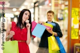 A young woman is shopping with her boyfriend carrying many shopping bags; copyright: PantherMedia/gpointstudio
