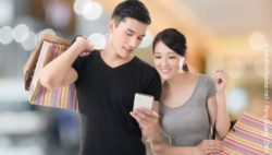 Photo: Shopping couple looking at a smartphone; copyright: panthermedia.net / PengGuang Chen
