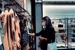 A woman wearing a mask looking at clothes in a store; copyright: Arturo Rey/Unsplash