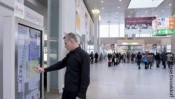photo: Man using an information touchpoint ; coypright: Messe Düsseldorf