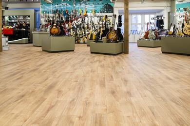 Vinyl meets music: the wood designs on the floor space make for pleasantly low-key flooring next to the music instruments.