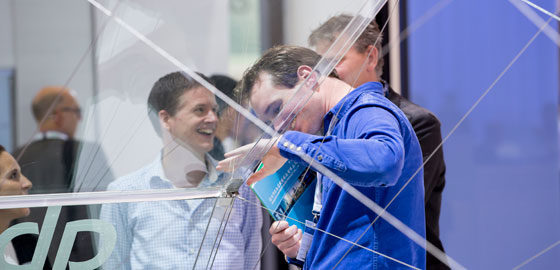 People behind a glass construction; copyright: Messe Düsseldorf/glasstec
