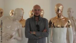 Image: A bald man with folded arms. Around him are standing white-golden mannequins; Copyright: Hans Boodt Mannequins