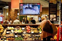 Fruit and vegetable counter at REWE with large screen running a live stream; copyright: Online Software AG / REWE Richrath