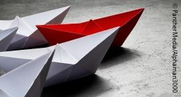 Photo: Several white paper boats following a red paper boat; Copyright: PantherMedia/Alphaman3000