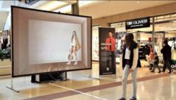 Image: Big screen in a shop. A young woman is standing infront of it; Copyright: Luigi Bucchino