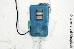 Blue electricity meter with black cable on grey wall; copyright: taner ardalı/Unsplash