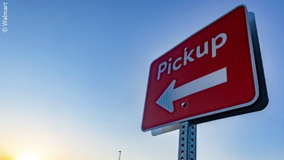 "A red sign in front of a blue sky, on which ""pickup"" is written with an arrow; copyright: Walmart"