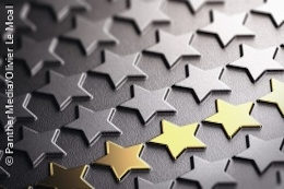 A row of golden stars in a field of black stars made of metal