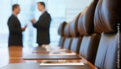 Photo: Conference table and two people talking in background; copyright: panthermedia.net / londondeposit