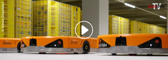 Several flat robots in front of yellow shelves; copyright: Messe Düsseldorf