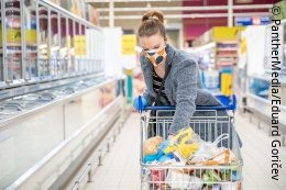 A young woman is grocery shopping with her shopping cart and a face mask; copyright: PantherMedia/Eduard Goričev