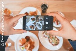 Person taking a picture of their food with a smartphone; copyright: Eaters Collective/Unsplash