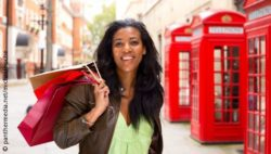Photo: Woman with shopping bags, behind her red phone box; copyright: panthermedia.net/michaelpuche