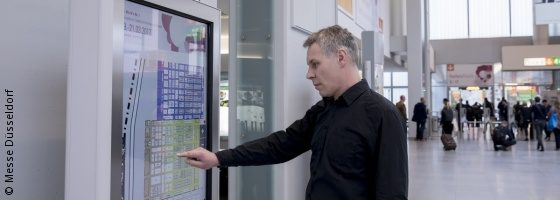 Photo: exhibitor using info touchpoint that is equipped with beacons; copyright: Messe Düsseldorf