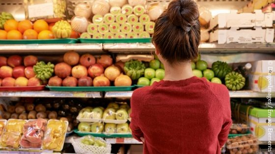 A young woman stands in front of a fruit and vegetable shelf in a supermarket; copyright: DragonImages / Envato Elements