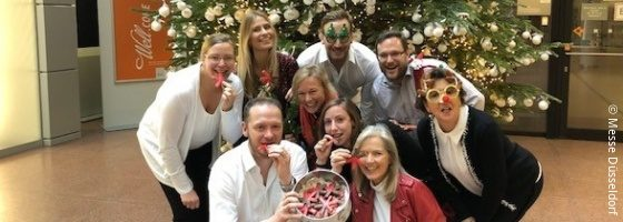 Several people, partly in disguise, with star-shaped cookies in a group photo in front of a christmas tree.
