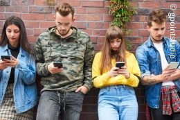 Four young people lean against a wall and operate their smartphones; copyright: gpointstudio