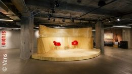 Photo: An empty warehouse room with a small stage and two red chairs; copyright: Vans; Copyright: Vans