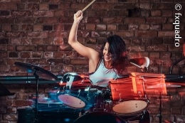 A young woman plays enthusiastically on a drum set; copyright: fxquadro
